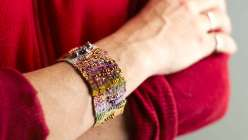 """Liz Smith teaches a freeform approach to looming, showing you how to set up a loom and basic weaving techniques with her """"over, under, over under"""" mantra. You design as you go, resulting in a modern asymmetrical, textured cuff."""