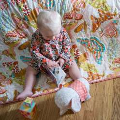 Anna Maria Horner teaches you the entire process of creating a baby quilt, from laying out and basting, then highlighting the design of a printed fabric with even stitching, and finally binding the quilt with single fold bias binding.